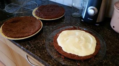 Die Orangen-Frischkäse-Creme auf dem untersten und dem mittleren Boden verteilen und am Rand etwas Platz aussparen, damit möglichst wenig aus der Torte rausläuft.